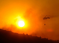An helicopter drops water on a wildfire burning near Aliaga, Teruel. Some 500 people were battling another wind-fuelled wildfire in northeastern Spain which claimed the lives of four firefighters and seriously injured two others. Temperatures were forecast to reach 41 degrees Celsius (105 degrees Fahrenheit) in many parts of Spain on Wednesday, raising the risk that more wildfires could break out. on July 23, 2009. (C) Pedro ARMESTRE