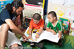 Education Preschool 3-5 year olds male teacher reading picture book to two boys horizotnal
