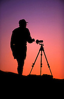 A photographer and camera tripod in silhouette at dawn.