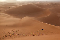 A visitor to the Sahara collapses, exhausted after jumping into the dunes and walking up them numerous timesin the Erg Chegaga region of the Sahara in Morocco.