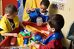 Educaton preschool  3-4 year olds water table group of three boys playing horizontal