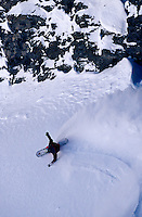 Aerial view of a fast downhill running snowboarder.