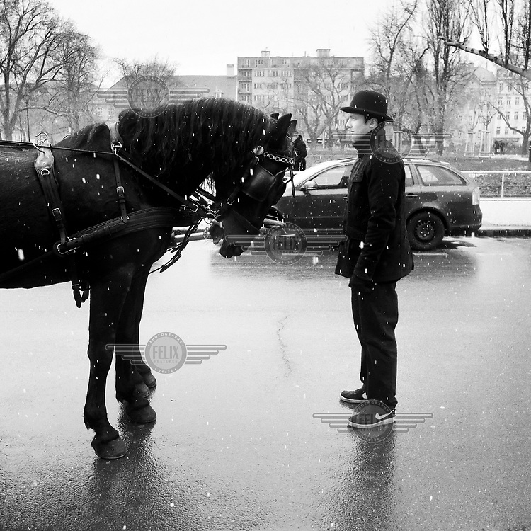 A man stands in the snow with a horse during the Masopust carnival (Mardi Gras).