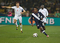 The USA's Robbie Findley dribbles upfield as England's Steven Gerrard (4) looks on in the first half of the 2010 World Cup match between USA and England in Rustenberg, South Africa on Saturday, June 12, 2010.
