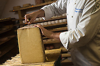 France, Haute-Garonne (31), Toulouse, Fromagerie Xavier :  François Bourgon, fromager affineur avec une fourme de Laguiole ,  dans sa cave d'affinage  // France, Haute Garonne, Toulouse,  Fromagerie Xavier , François Bourgon, cheesemonger with Laguiole cheese in its maturing cellar