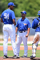 GCL Blue Jays pitching coach Willie Collazo (17) talks with pitcher Angel Perdomo (51) during a game against the GCL Yankees 2 on July 2, 2014 at the Bobby Mattick Complex in Dunedin, Florida.  GCL Yankees 2 defeated GCL Blue Jays 9-6.  (Mike Janes/Four Seam Images)