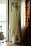 The bride's wedding dress hangs in the doorway.