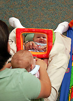 Infant looks in mirror with caregiver.