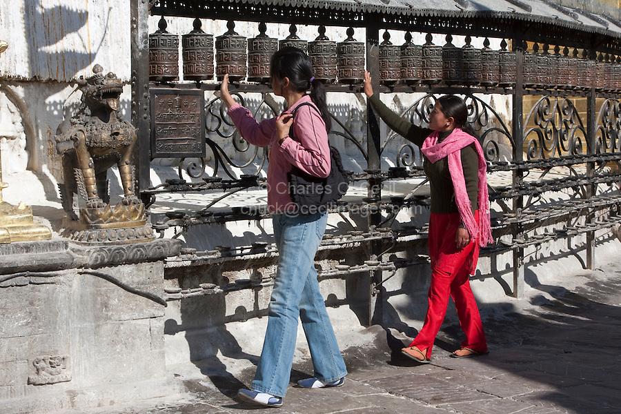 Kathgmandu, Nepal.  Nepali Women Spinning Prayer Wheels at Swayambhunath Temple.