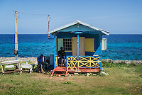 Local men sit in the shade of a seaside shack, Jamaica