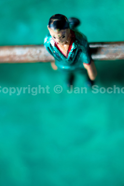 A table football player figure, with a painted turquoise shirt, is seen inside the table football box on the street of Olmedo, a small village in the mountains of Ecuador, 27 June 2010. Table football, also known as futbolin in Latin America, is a widely popular table-top game in Ecuador. During the annual fairs, the rusty old outdoor-designed tables, fully ocuppied by excited children, may be found on all public places, particularly on the squares and in the parks. Human players use figures mounted on rotating bars to kick the small plastic ball into the opposing goal. Each team of 1 or 2 human players controls 4 rows on its side of the table. The game ends when one team scores a predetermined number of goals. In 2002, the International Table Soccer Federation (ITSF) was established to promote the sport of table football.