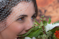 A bride smiles at her husband through her bouquet.