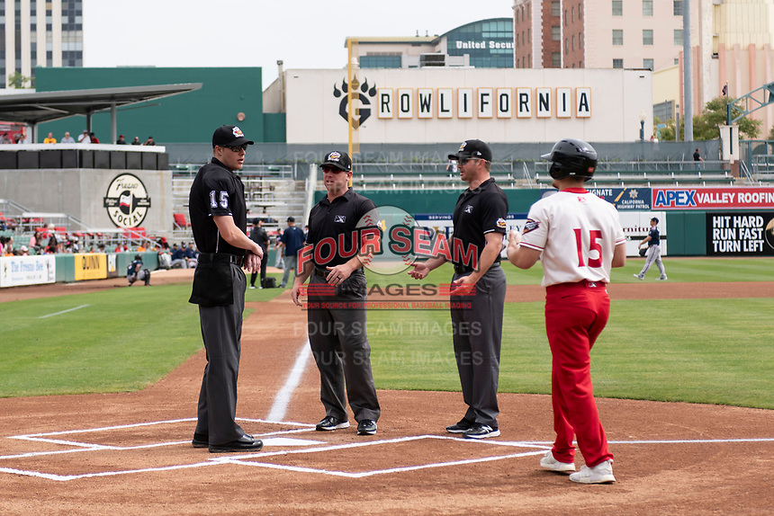Home plate umpire Clint Vondrak meets with field umpires Bryan Fields and Sean Allen before a game between the Reno Aces and the Fresno Grizzlies at Chukchansi Park on April 8, 2019 in Fresno, California. Fresno defeated Reno 7-6. (Zachary Lucy/Four Seam Images)