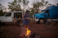 Joanna Atkins peeling an onion, preparing dinner at a campsite on the side of the Gibb River road.