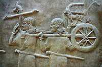 Stone relief sculptured panel of soldiers carrying a chariot . Facade L. Inv AO 19884 from Dur Sharrukin the palace of Assyrian king Sargon II at Khorsabad, 713-706 BC.  Louvre Museum Room 4 , Paris