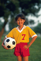 Smiling portrait of a young Asian-American girl in a soccer uniform holding a soccer ball.