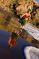 Solo hula dancer at the water's edge with her reflection at Olowalu, Maui.