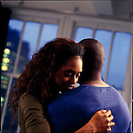 African American couple embracing with windows in background
