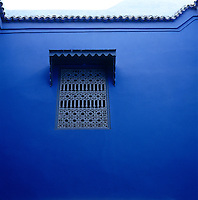 In the vibrant blue wall of a traditional Moroccan riad an ornamental grille creates an interesting focal point