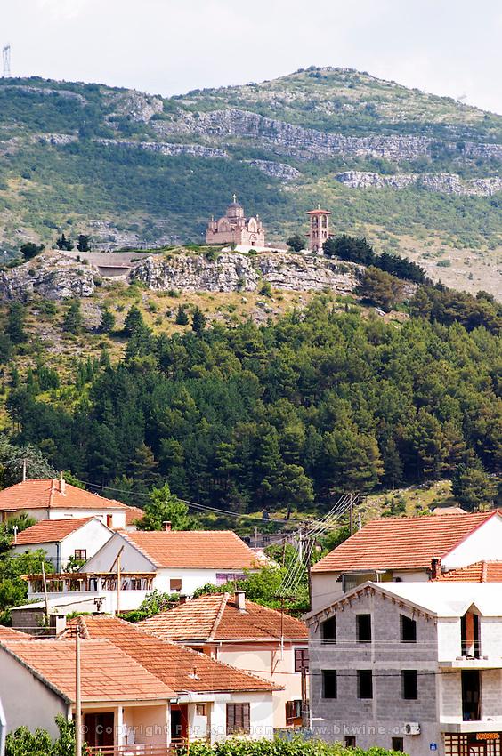 Street scene in Trebinje, the monastery Gracanica on the historic hill known as Crkvina in the background. Houses and construction sites. Trebinje. Republika Srpska. Bosnia Herzegovina, Europe.