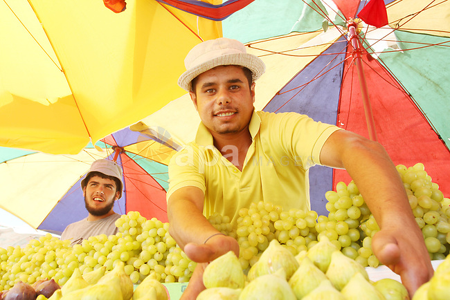 Palestinian vendors sell summer fruits during the selling season at Sheikh Ajlin market, in Gaza city on August 11, 2021. Palestinian farmers told that the output of the harvests of fruits this year is lower than forecast compared with the production of last year, which was affected by the change in weather conditions. Photo by APA