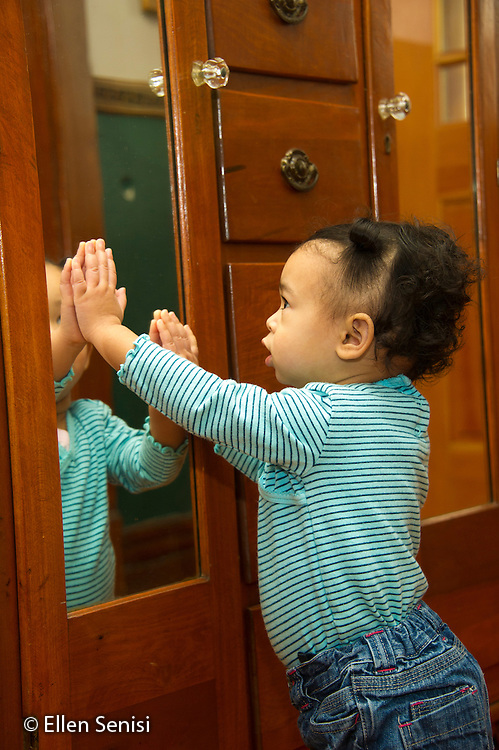MR / Schenectady, NY. Toddler (1 year and 2 months old, African-American and Caucasian) looks carefully at her mirror image. MR: Dal4. ID: AM-HD. © Ellen B. Senisi