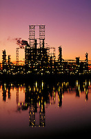 Catalyst cracker at oil refinery reflecting in pond