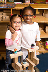 Preschool ages 3-5 two girls friends pose proudly with building they made from wooden blocks vertical