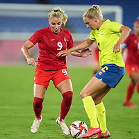 YOKOHAMA, JAPAN - AUGUST 6: Adriana Leon #9 of Canada and Jonna Andersson #2 of Sweden battle for the ball during a game between Canada and Sweden at International Stadium Yokohama on August 6, 2021 in Yokohama, Japan.