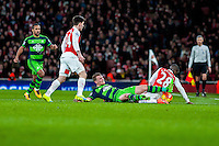 Stephen Kingsley of Swansea City  fights for the ball on the floor during the Barclays Premier League match between Arsenal and Swansea City at the Emirates Stadium, London, UK, Wednesday 02 March 2016