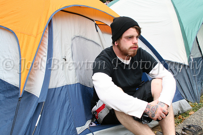 """Bud Ferguson, 21, of Pittsburgh settles down after attempting to find a laundromat to dry out his belongings which were soaked by the rain the previous night. """"I'm here fighting the corporate greed, man. I'm just trying to make a better America for my son."""""""