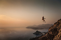 A rock climber hangs on rope while being lowered down at sunset, Kalymnos, Greece