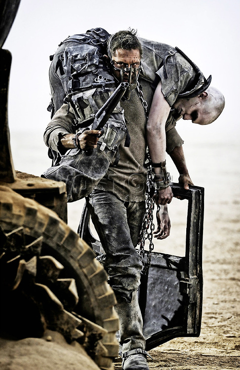"NEW PICTURES TOM HARDY IN MAD MAX FURY ROAD MOVIE <br /> <br /> From director George Miller, originator of the post-apocalyptic genre and mastermind behind the legendary ""Mad Max"" franchise, comes ""Mad Max: Fury Road,"" a return to the world of the Road Warrior, Max Rockatansky.<br /> <br /> Haunted by his turbulent past, Mad Max believes the best way to survive is to wander alone. Nevertheless, he becomes swept up with a group fleeing across the Wasteland in a War Rig driven by an elite Imperator, Furiosa. They are escaping a Citadel tyrannized by the Immortan Joe, from whom something irreplaceable has been taken. Enraged, the Warlord marshals all his gangs and pursues the rebels ruthlessly in the high-octane Road War that follows.<br /> <br /> Tom Hardy (""The Dark Knight Rises"") stars in the title role in ""Mad Max: Fury Road""—the fourth in the franchise's history. Oscar winner Charlize Theron (""Monster,"" ""Prometheus"") stars as the Imperator, Furiosa. The film also stars Nicholas Hoult (""X-Men: Days of Future Past"") as Nux; Hugh Keays-Byrne (""Mad Max,"" ""Sleeping Beauty"") as Immortan Joe; and Nathan Jones (""Conan the Barbarian"") as Rictus Erectus. Collectively known as The Wives, Zoë Kravitz (""Divergent"") plays Toast, Riley Keough (""Magic Mike"") is Capable, Rosie Huntington-Whiteley (""Transformers: Dark of the Moon"") is Splendid, and supermodel Abbey Lee is The Dag, and Courtney Eaton is Fragile. Also featured in the movie are Josh Helman as Slit, Jennifer Hagan as Miss Giddy, and singer/songwriter/performer iOTA as Coma-Doof Warrior.<br /> <br /> Picture shows: Max ( Hardy ) carries off one of the henchmen of  warlord Immortan Joe as he escapes from their clutches.<br /> 75596<br /> EDITORIAL USE ONLY"