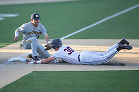 Michigan Wolverines third baseman Christian Molfetta (14) tags out Connecticut baserunner Chris Brown (30) at third  during the NCAA baseball tournament on June 4, 2021 at Frank Eck Stadium in Notre Dame, Indiana. The Huskies defeated the Wolverines 6-1. (Andrew Woolley/Four Seam Images)