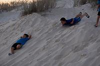 Children play on dunes at White Sands National Monument near Alamogordo, New Mexico, USA, on Fri., Dec. 29, 2017.