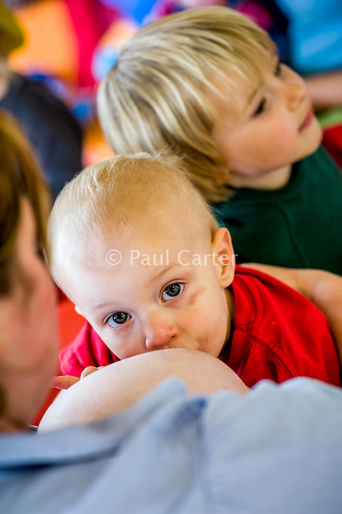 "A woman breastfeeding her little boy who is sitting on her lap at a breastfeeding advice and support drop-in centre. His older brother is in the background.<br /> <br /> Image from the ""We Do It In Public"" documentary photography project collection: <br />  www.breastfeedinginpublic.co.uk<br /> <br /> Hampshire, England, UK<br /> 13/06/2012"