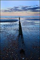 Man walking along a groyne on the beach