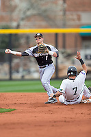 Cole Fabio (1) of the Bryant Bulldogs turns a double play as Zach Remillard (7) of the Coastal Carolina Chanticleers slides into second base at Springs Brooks Stadium on March 13, 2015 in Charlotte, North Carolina.  The Chanticleers defeated the Bulldogs 7-2.  (Brian Westerholt/Four Seam Images)