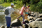 Our guide, Juan Luis (left)  and Rosita (right) help Libby cross the boulders over the Yaro River during the early moments of our trek up the mountain.