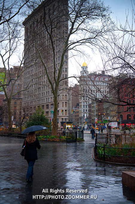 Lady walk under rain in Madison Square park to Flatiron building, Manhattan, NYC