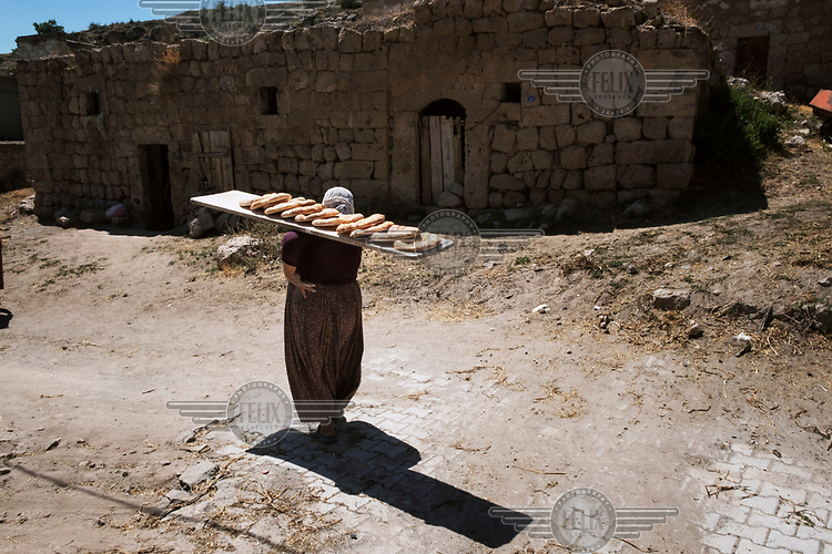 A woman carries a wooden board on her shoulder laden with freshly baked loaves of flat bread.