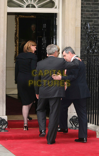 SARAH BROWN, PRESIDENT GEORGE W. BUSH, GORDON BROWN PM .President Bush and his wife Laura visit the Prime Minister Gordon Brown and his wife Sarah Brown for an informal dinner on Bush's farewell tour, 10 Downing Street, London, England, .15th June 2008.full length red carpet going inside door doorway hand arm around shoulder back rear behind.CAP/DS.©Dudley Smith/Capital Pictures