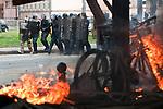 Des policiers patrouillent devant un batiment brule par des casseurs pendant la manifestation du 4 avril 2009 contre le sommet de l'OTAN a Strasbourg. Dans ce quartier populaire du Port Autonome, un hotel, une pharmacie, l'ancien bureau des douanes seront incendies et une station service saccagee..Credit;Hughes Leglise-Bataille/Julien Muguet/face to face