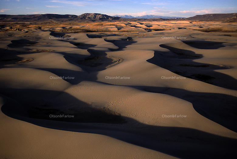 Shadows fall on sand dunes in the Red Desert, one of 15 most endangered wild lands according to the Wilderness Society.  Nearby oil and gas development threatens the 600,000 acre national treasure.  The high-desert landscape is range for 50,000 pronghorn antelope and a rare desert elk herd.