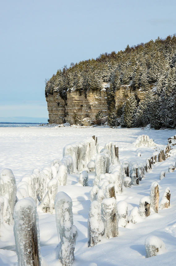 Fresh snow on old pilings and the nearby limestone cliffs. Fayette State Park, Garden Peninsula.