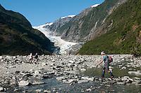 A tramper crossing a stream in a valley on his way towards Franz Josef Glacier - Westland National Park, West Coast