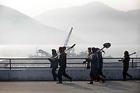 Korean women walk along the road carrying shovels on the outskirts of Pyongyang, North Korea (DPRK) on 29 February 2008.