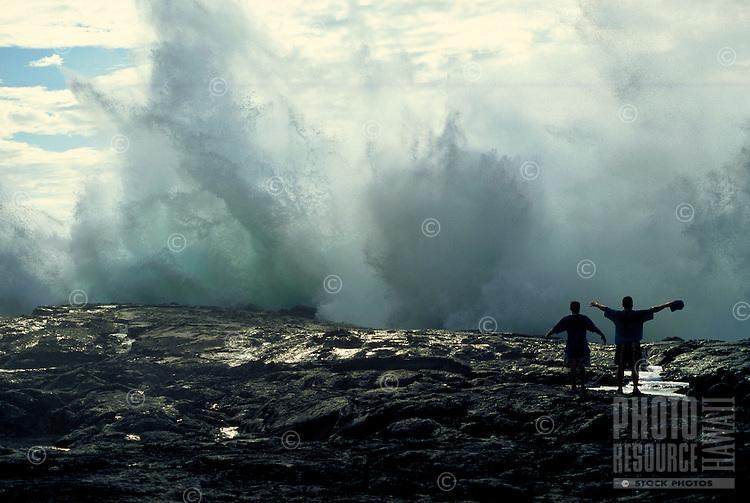 Teens enjoy the thrill of huge crashing waves on the black lava rocks on the Big Island of Hawaii.