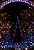 London, England. The London Eye at night. Purple and blue lights.