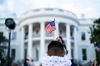 A child waves an American flag during a Fourth of July celebration with frontline workers and military families, Sunday, July 4, 2021, on the South Lawn of the White House. (Official White House Photo by Chandler West)